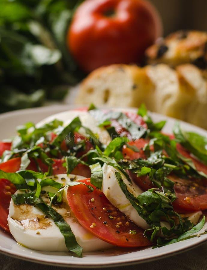 Caprese sallad med tomater, basilika och mozzarellaost, med bröd och jordbruksprodukter i bakgrund arkivfoto