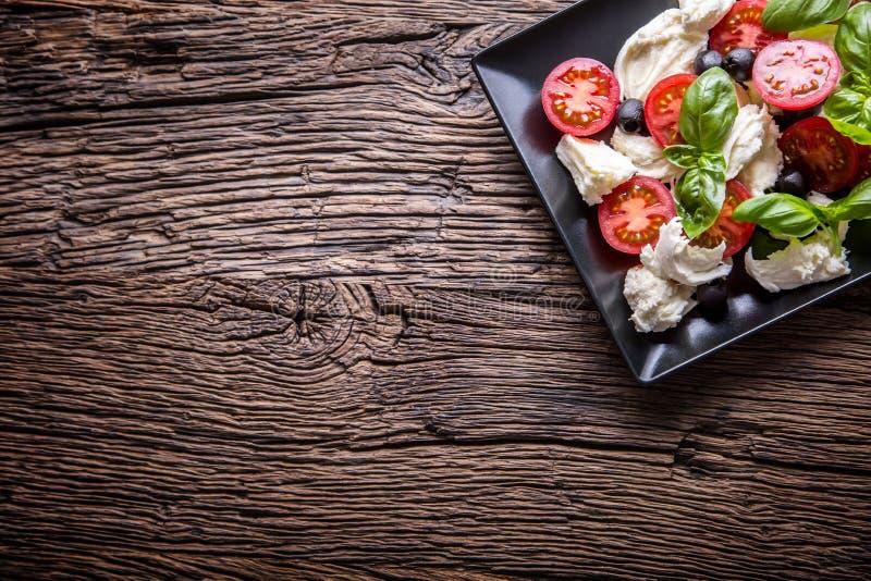 caprese sallad Medelhavs- sallad Körsbärsröda tomater basilika och olivolja för Mozzarella på den gamla ektabellen lyx för livsst arkivbilder