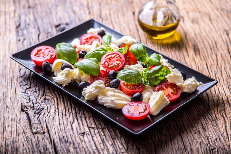 caprese sallad Medelhavs- sallad Körsbärsröda tomater basilika och olivolja för Mozzarella på den gamla ektabellen lyx för livsst royaltyfri foto