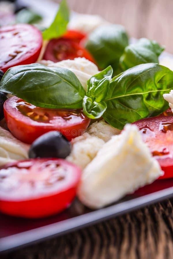 caprese sallad Medelhavs- sallad Körsbärsröda tomater basilika och olivolja för Mozzarella på den gamla ektabellen lyx för livsst royaltyfri fotografi