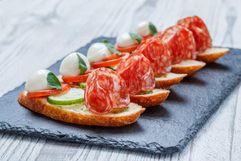 Caprese-Sandwiche mit Tomate, Mozzarellakäse, Basilikum, Salami auf ciabatta Brot auf Steinschieferhintergrundabschluß oben stockbild