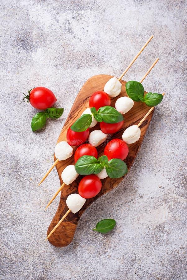 Capresevleespennen met mozarella, tomaten en basilicum stock foto's