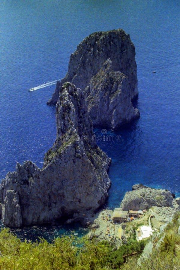 CAPRI, ITÁLIA, 1970 - o mar azul de Capri cerca seu Faraglioni famoso fotos de stock