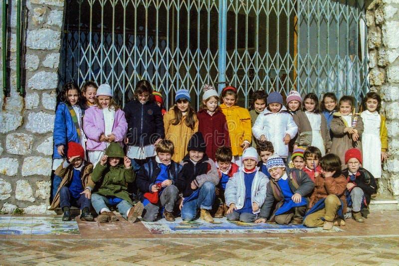 CAPRI, ITÁLIA, 1987 - um grupo de alunos sorri, em uma rua em Capri, no sol morno do inverno no fim de seu dia escolar imagem de stock royalty free