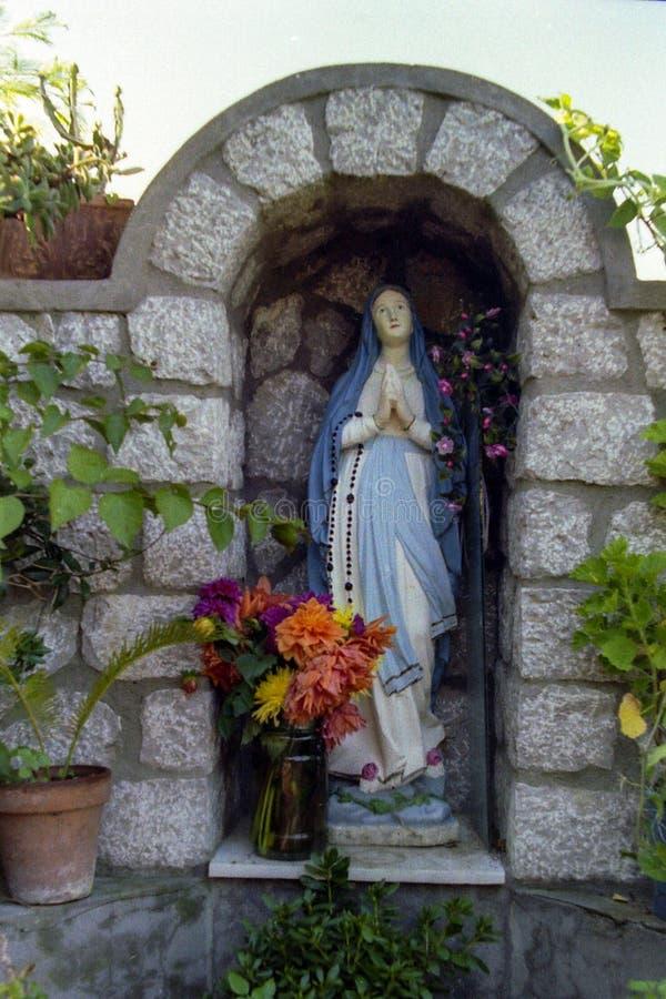 CAPRI, ITÁLIA, 1983 - uma estátua pequena de Madonna abençoa transeuntes ao longo de uma rua em Anacapri imagem de stock royalty free