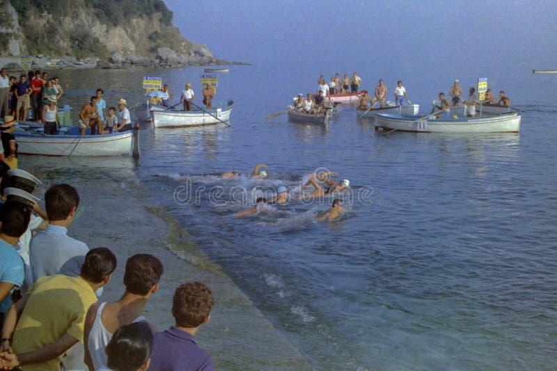 CAPRI, ITALIË, 1967 - de Mensen wonen het vertrek van de atleten in de marathon Capri-Napels in het hele land in de wateren van  stock afbeeldingen