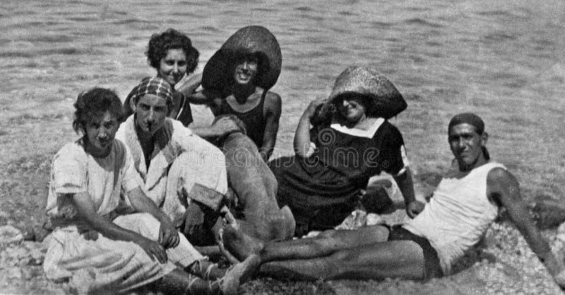 Capri, Italië, 1932 - een groep jongens en de meisjes met een hond ontspannen in de Capri-zon stock foto