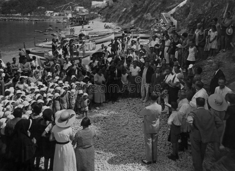 Capri, Italië, 1921 - een herdenkingsceremonie met openbare en godsdienstige diensten onder de zwemmers op het strand van Jachtha stock afbeeldingen