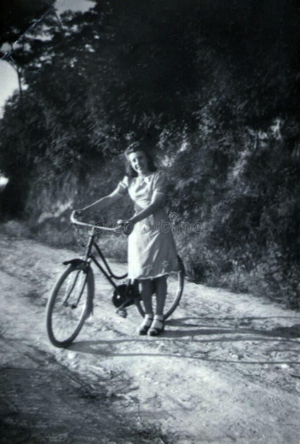 Capri, Italië, 1932 - een meisje glimlacht cheerfully met haar fiets royalty-vrije stock foto