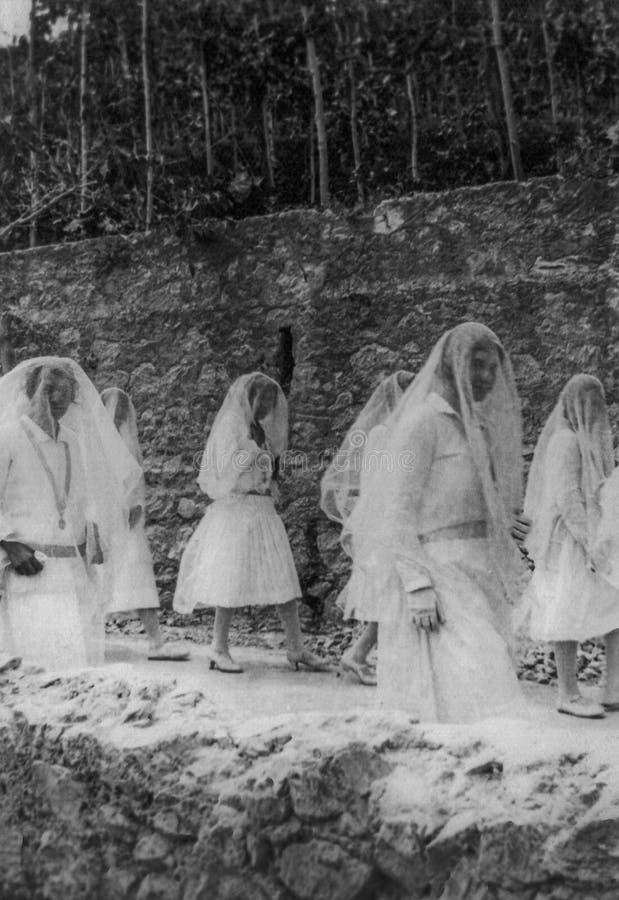 Capri, Italië, 1929 - Sommige jonge meisjes paraderen in witte kleding en versluieren tijdens de vieringen van San Costanzo, patr stock foto