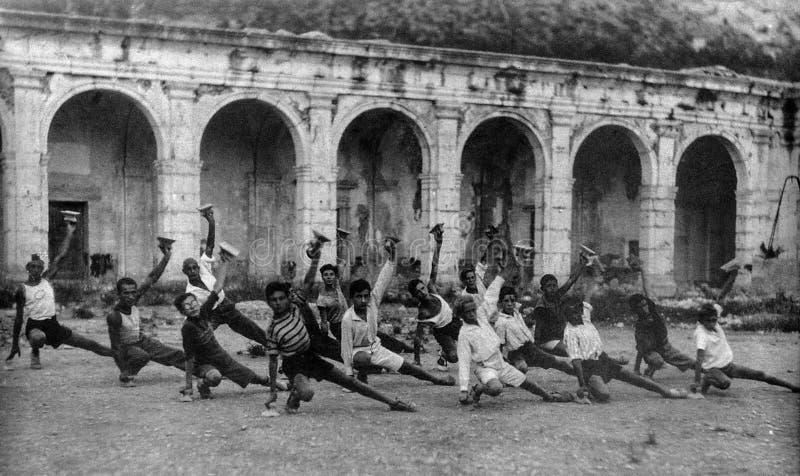 Capri, Itali, 1927 - los italianos jovenes hacen ejercicios gimnásticos en el Certosa de Capri durante el fascismo fotografía de archivo libre de regalías