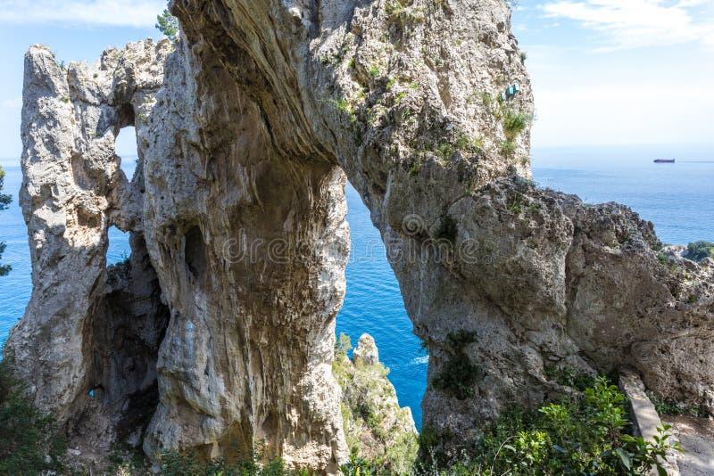Capri Italia, isla en un día de verano hermoso, con las rocas del faraglioni y el arco de piedra natural foto de archivo libre de regalías