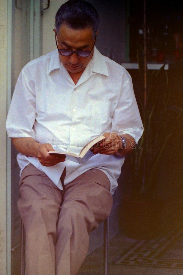 CAPRI, ITALIEN, 1970 - ein Mann liest sein absorbiertes Buch stockbild