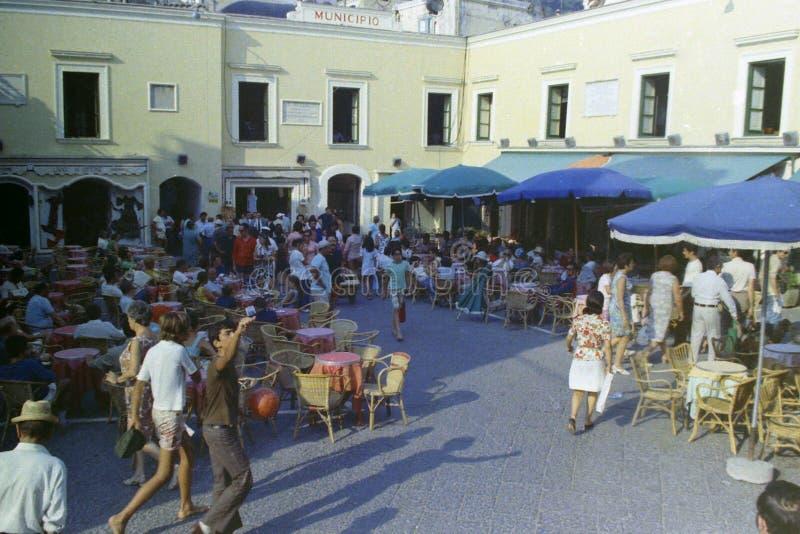 CAPRI ITALIEN, JULI 1965 - folket strosar bland stångtabellerna i den berömda Piazzettaen av Capri på en varm sommareftermiddag royaltyfria bilder
