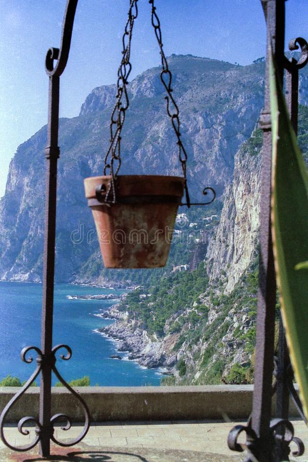 CAPRI, ITALY, 1986 - A caprese crock pot enjoys the spectacle of nature between Mount Solaro and the rocky coast of Marina Piccola.  royalty free stock images