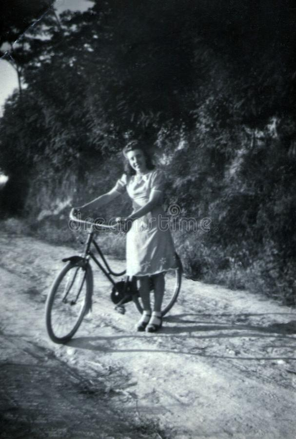 Capri, Italy, 1932 - A girl smiles cheerfully with her bicycle royalty free stock photo