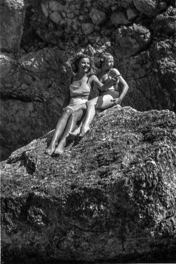 Capri, Włochy, 1932, Dwa pięknych dziewczyn na rockowym zawiadomieniu - coś ciekawi obraz royalty free
