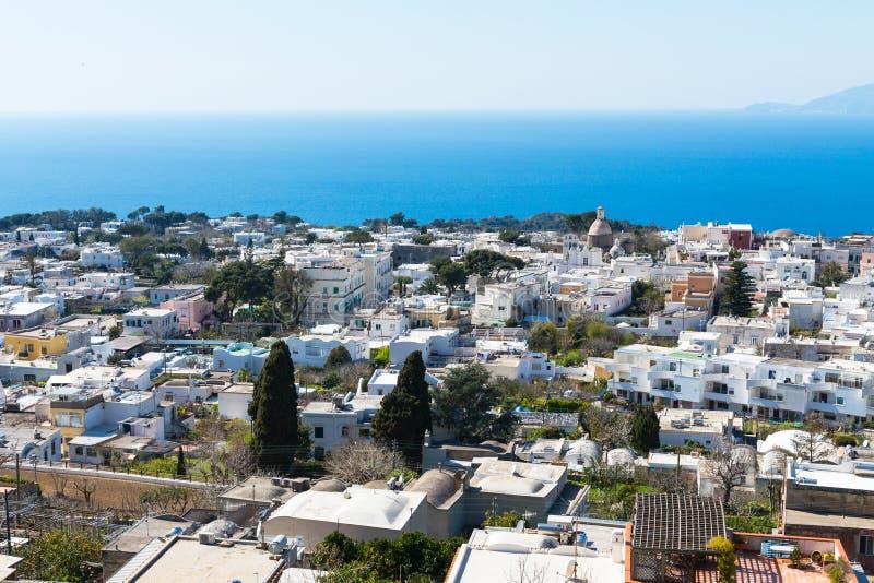 Capri, Włochy, z białymi domami, niebieskim niebem i niebieską wodą Widok góry Wezuwiusz zdjęcia stock
