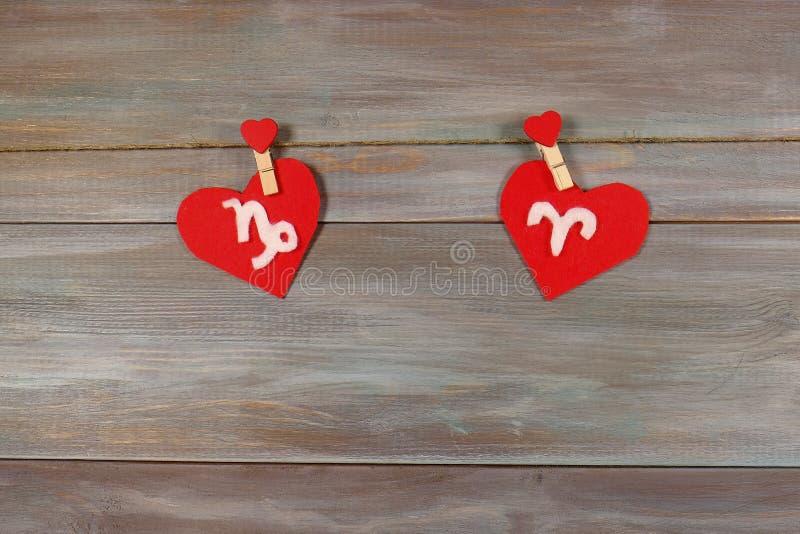 Capricórnio e Áries sinais do zodíaco e do coração backg de madeira imagem de stock royalty free