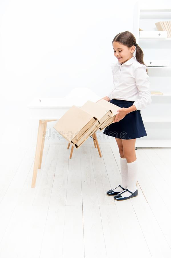 Capricious girl. smiling girl with workbook folders. Education. heavy documents. Towards knowledge. small girl in school. Uniform. lot of homework. Get stock image