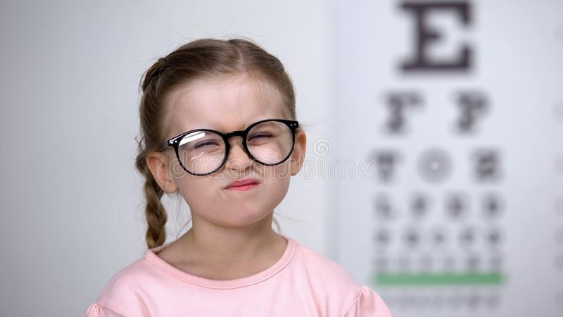 Capricious little girl afraid of eyeglasses, feeling insecure, vision correction. Stock photo stock photos