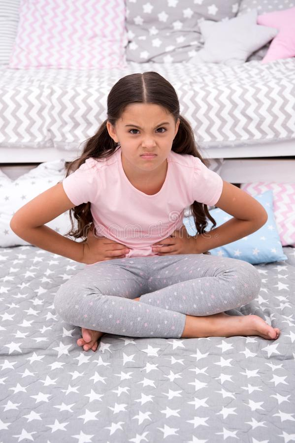 Capricious mood. Girl child sit in bedroom. Kid unhappy capricious someone entered her bedroom bothering . Girl kid long. Hair cute pajamas capricious face. Let royalty free stock photo