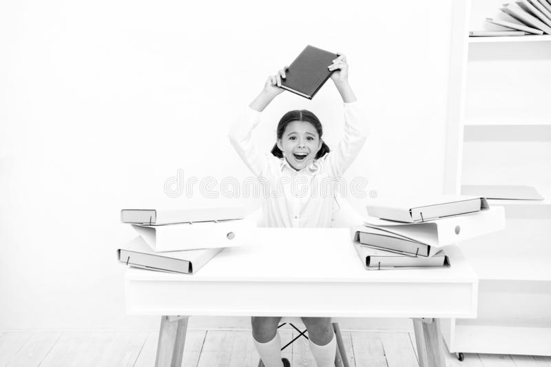 In capricious mood. Naughty child being noisy at school. Little child refusing to learn literacy. Small girl raising. Book over head. Angry girl hates reading royalty free stock photos