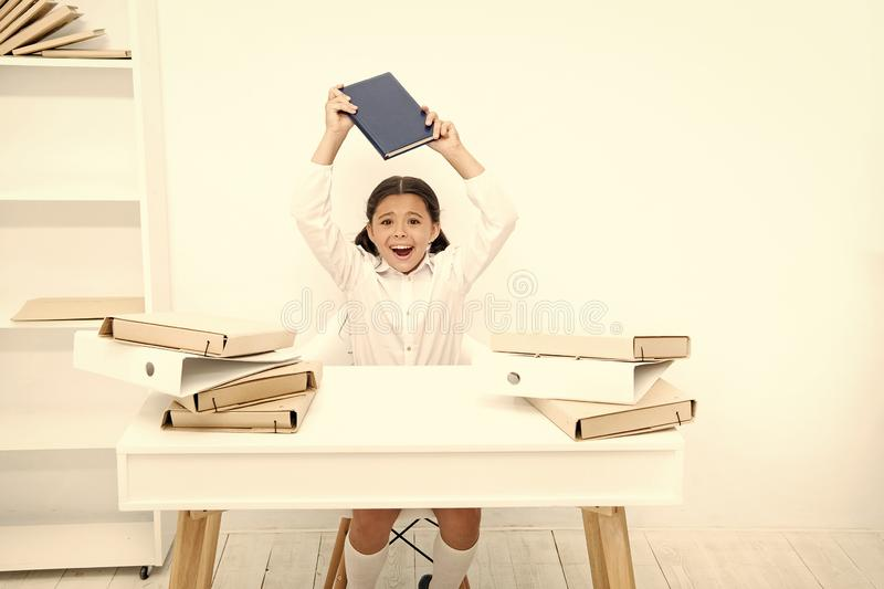In capricious mood. Naughty child being noisy at school. Little child refusing to learn literacy. Small girl raising. Book over head. Angry girl hates reading stock photography