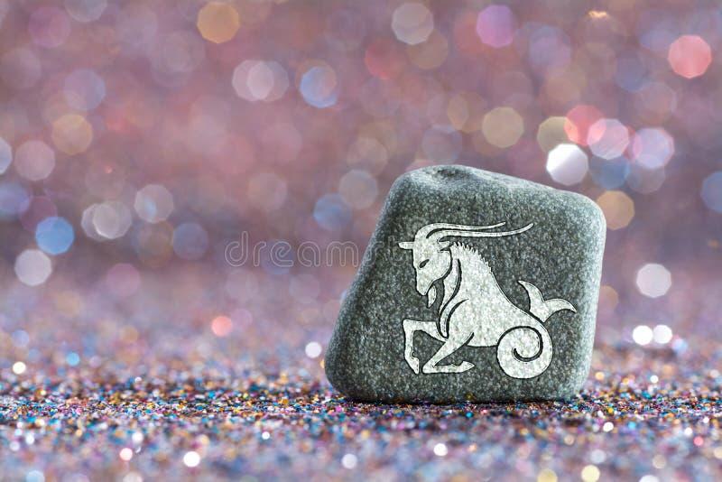 Capricorn zodiac sign. A green stone with Capricorn zodiac sign on glitter boke light background stock image