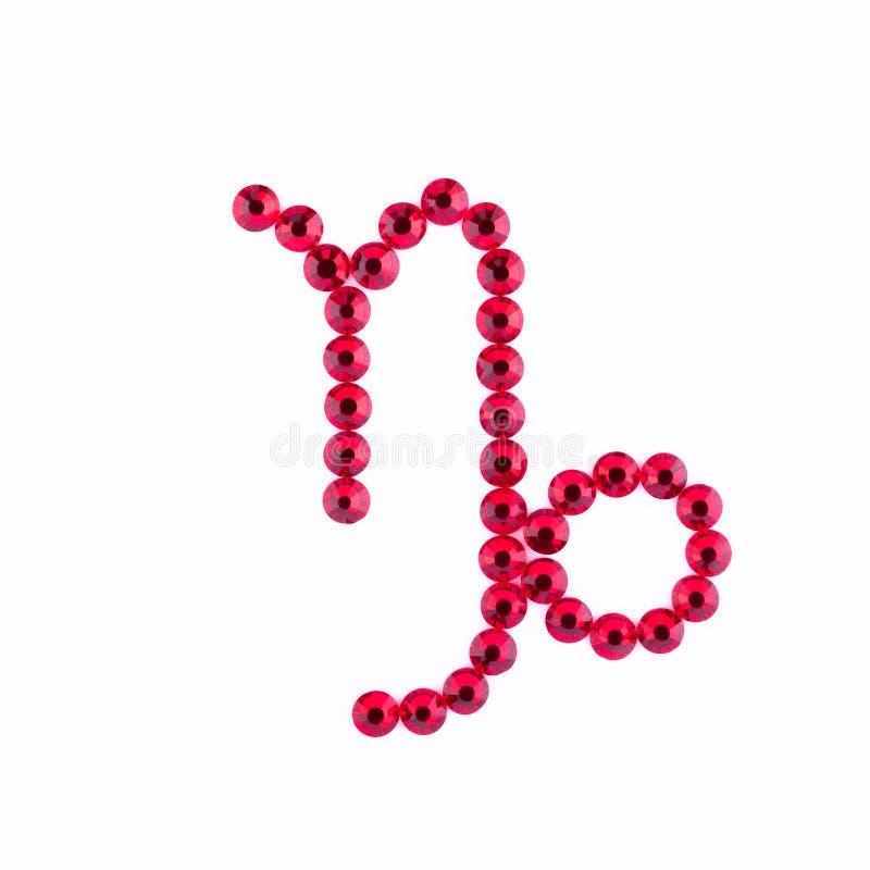 capricornio Muestra del zodiaco de diamantes artificiales rojos en una parte posterior del blanco imágenes de archivo libres de regalías