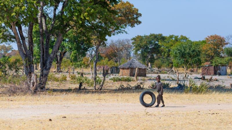 Caprivi Namibia, Sierpień, - 20, 2016: Biedny nastolatek bawić się na poboczu w wiejskim Caprivi pasku ludnościowy region wewnątr obraz royalty free