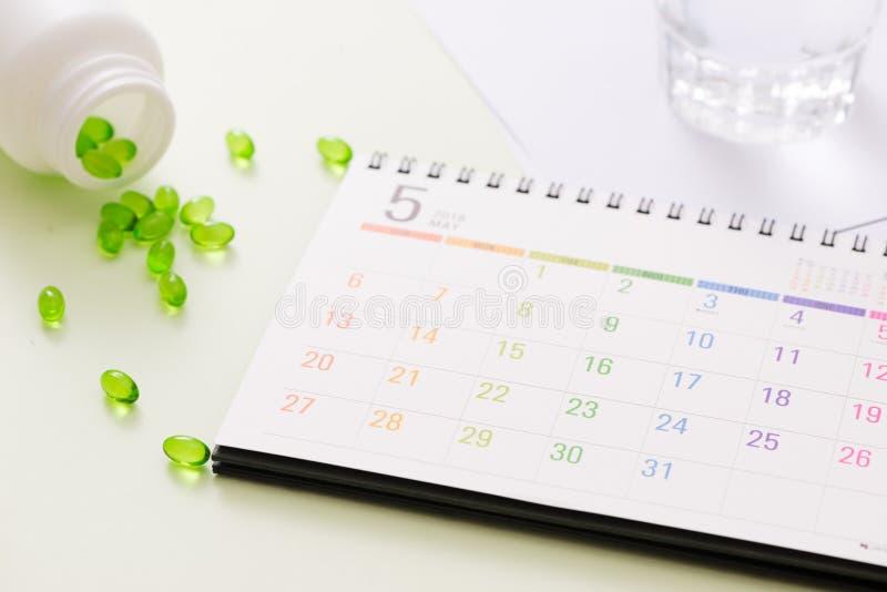 Capsula medica delle pillole in scatola della pillola con il calendario sul backgro bianco fotografia stock libera da diritti