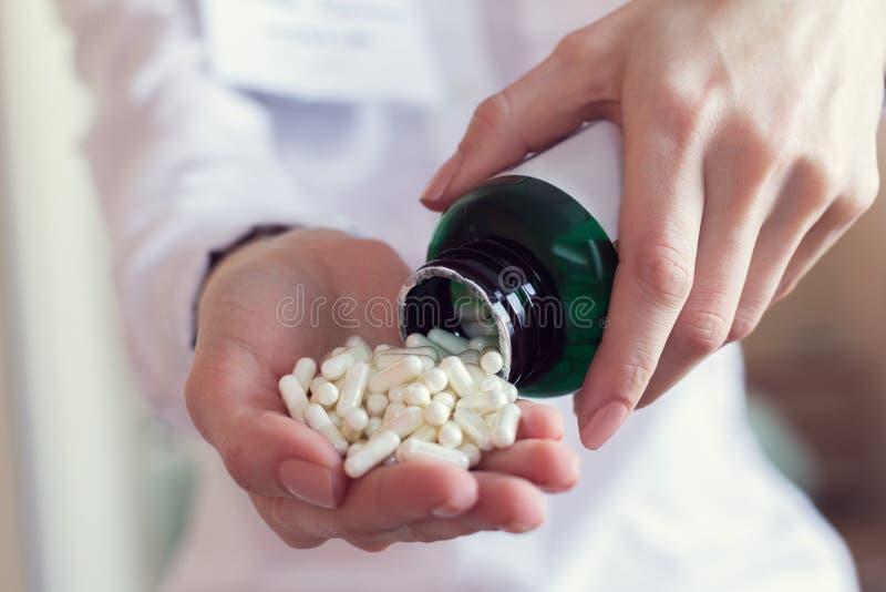Capsule bianche delle pillole in una mano del ` s di medico fotografie stock libere da diritti