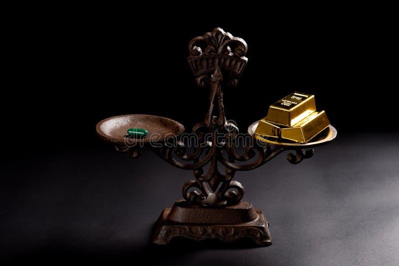 Capsule en goudstaven op evenwichtige schaal stock afbeeldingen