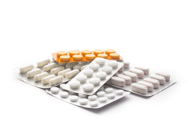 Capsule et pilules de plan rapproché dans le habillage transparent d'isolement sur le fond blanc Différents types de pilules photographie stock