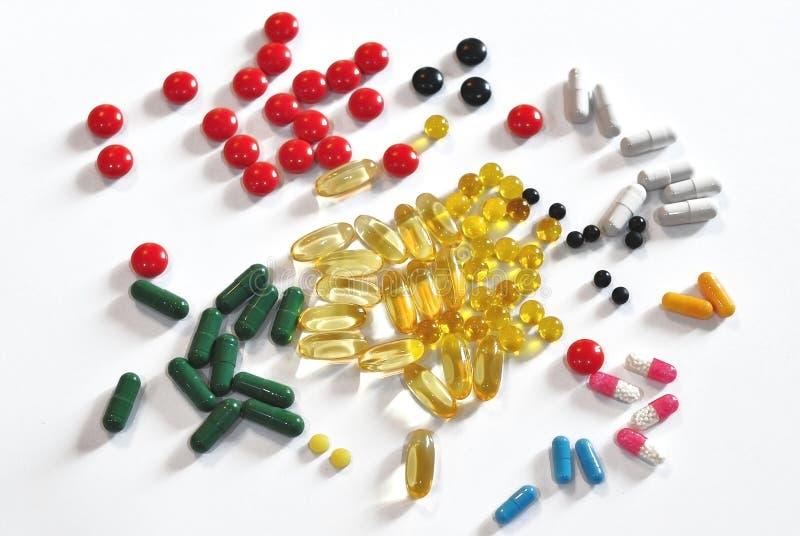 Capsule medicinali multicolori e compresse sparse sulla tavola fotografia stock libera da diritti