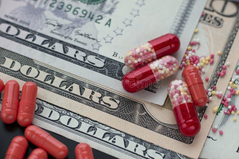 Capsule o pillole rosse sulle banconote in dollari fotografia stock libera da diritti