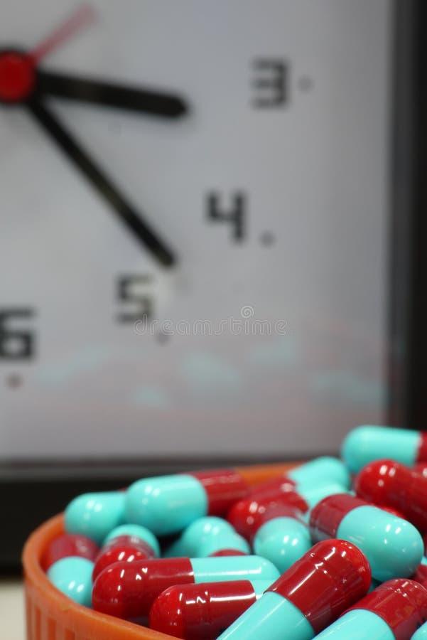 Capsule rouge et bleue avec le fond d'horloge images libres de droits