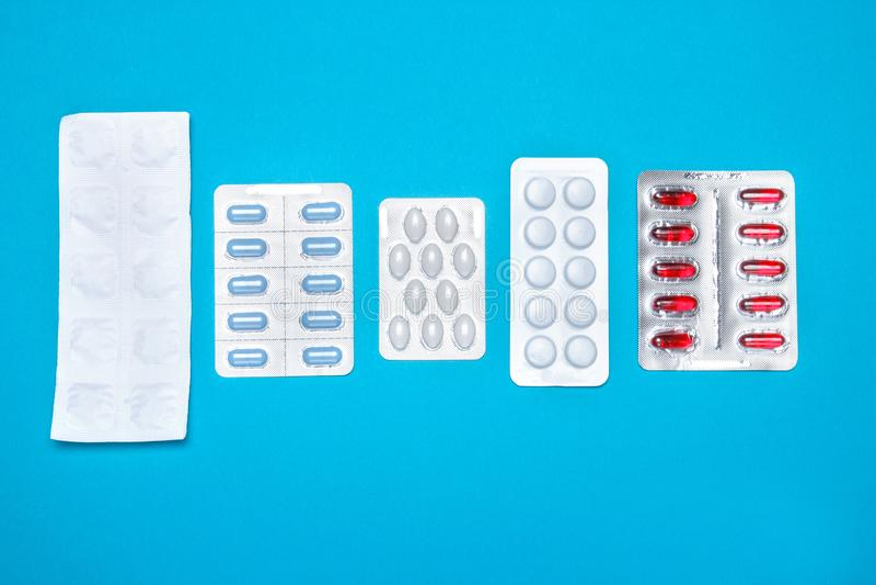 Capsulepillen in een blaarpak, op een blauwe achtergrond Het concept globale gezondheid Antibiotica, drugweerstand stock foto
