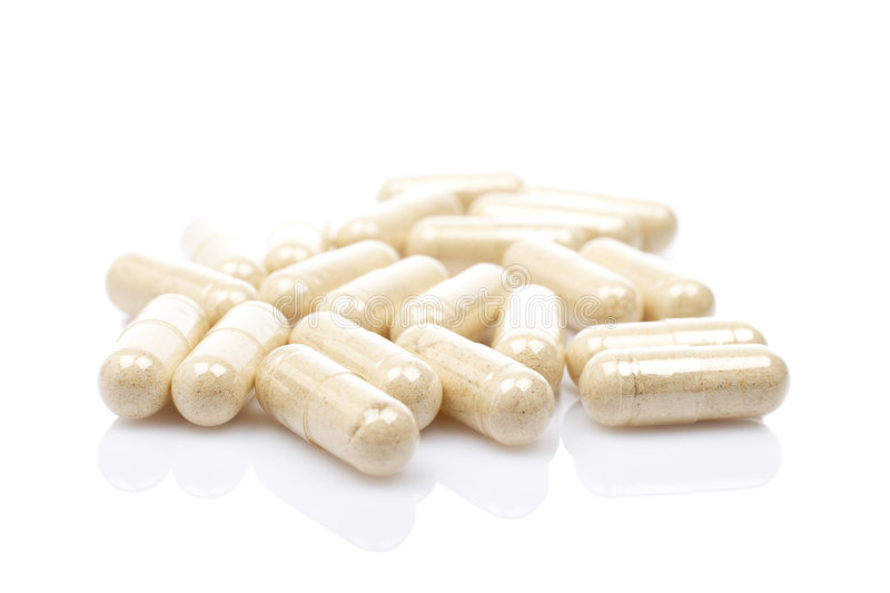 Capsules. Reflected on white background with shallow depth of field stock photos
