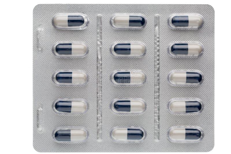 Capsules bleu-foncé et blanches de plan rapproché dans des habillages transparents de médicament images libres de droits