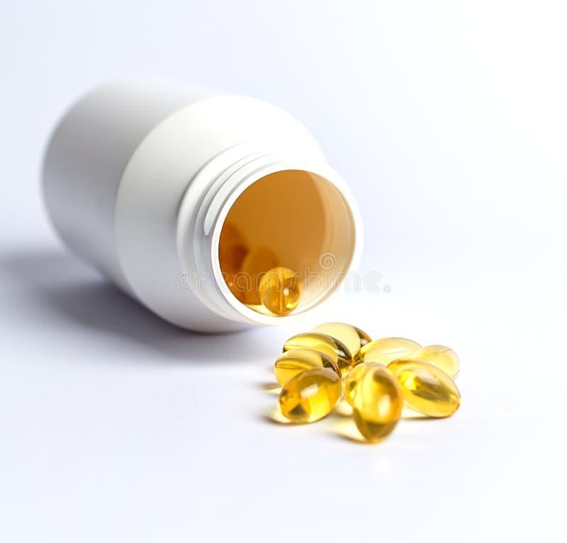 Capsules d'huile de poisson avec une bouteille de pilule blanche photographie stock libre de droits