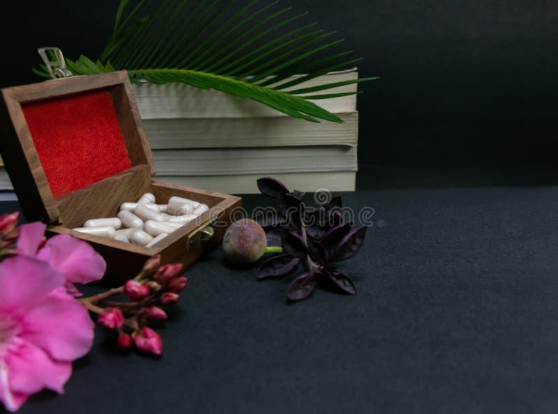Capsules de fines herbes dans la vieille boîte en bois avec la fleur rose, le fruit sauvage et la feuille verte sur des livres à  images stock