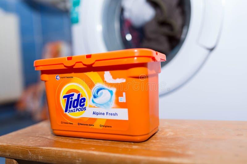 Capsules de liquide de lavage de marée devant une machine à laver image libre de droits