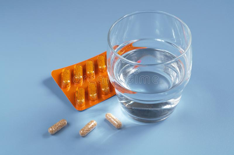Capsules and glass of water royalty free stock images