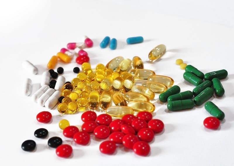 Capsules multicolores et comprimés médicinaux dispersés sur la table photographie stock libre de droits
