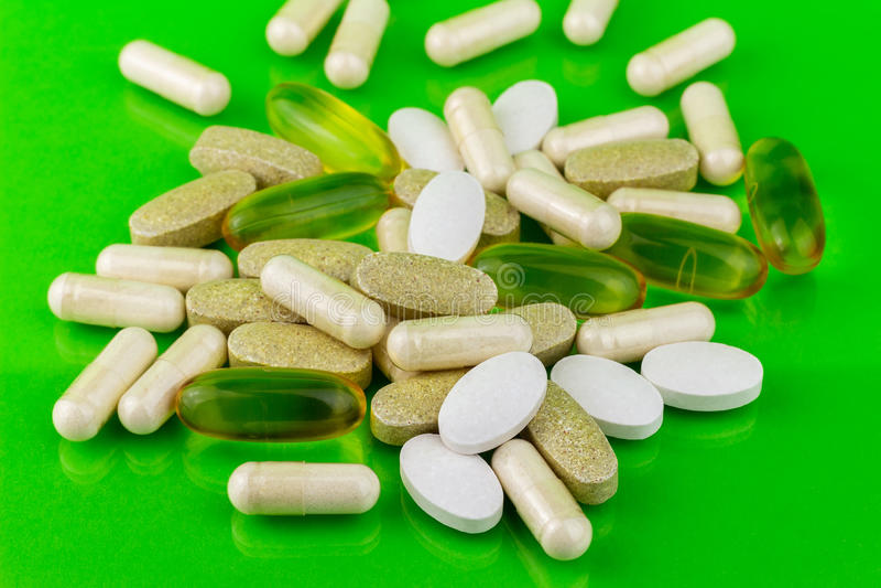 Capsules naturelles mélangées de pilules, d'Omega 3, de calcium, de multivitamin et de glucosamine de complément alimentaire sur  image libre de droits