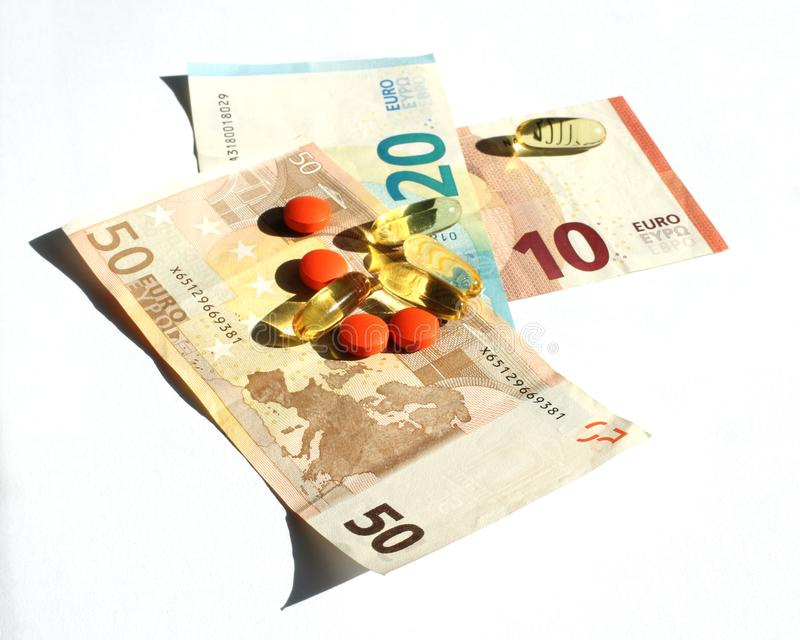 Capsules of omega 3 and orange tablets against pain laid on Euro banknotes. Pharmaceutical business stock photo
