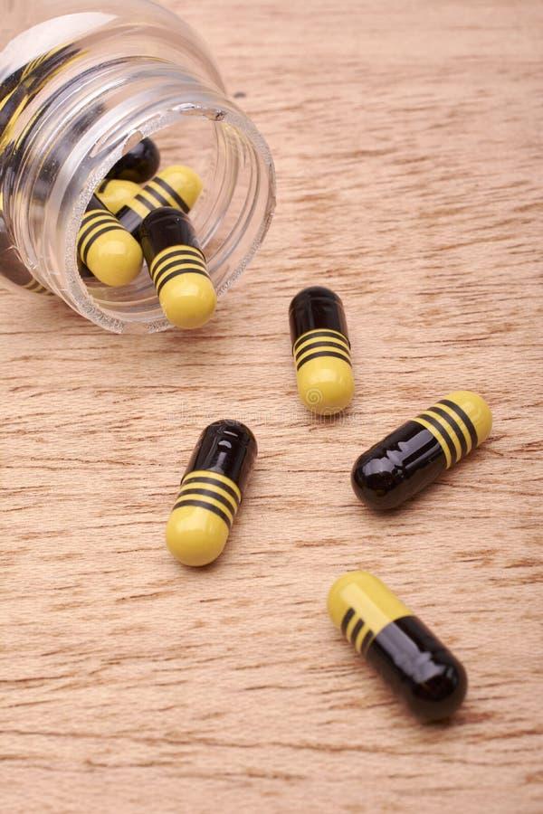 Capsules of pillen van geneesmiddel van transparante fles royalty-vrije stock afbeeldingen