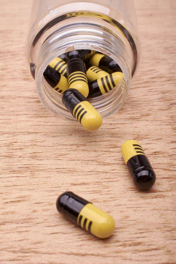 Capsules of pillen van geneesmiddel van transparante fles stock foto